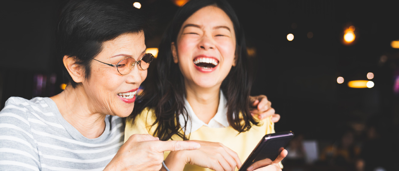 A young woman and her older mom laughing at something on a smartphone.