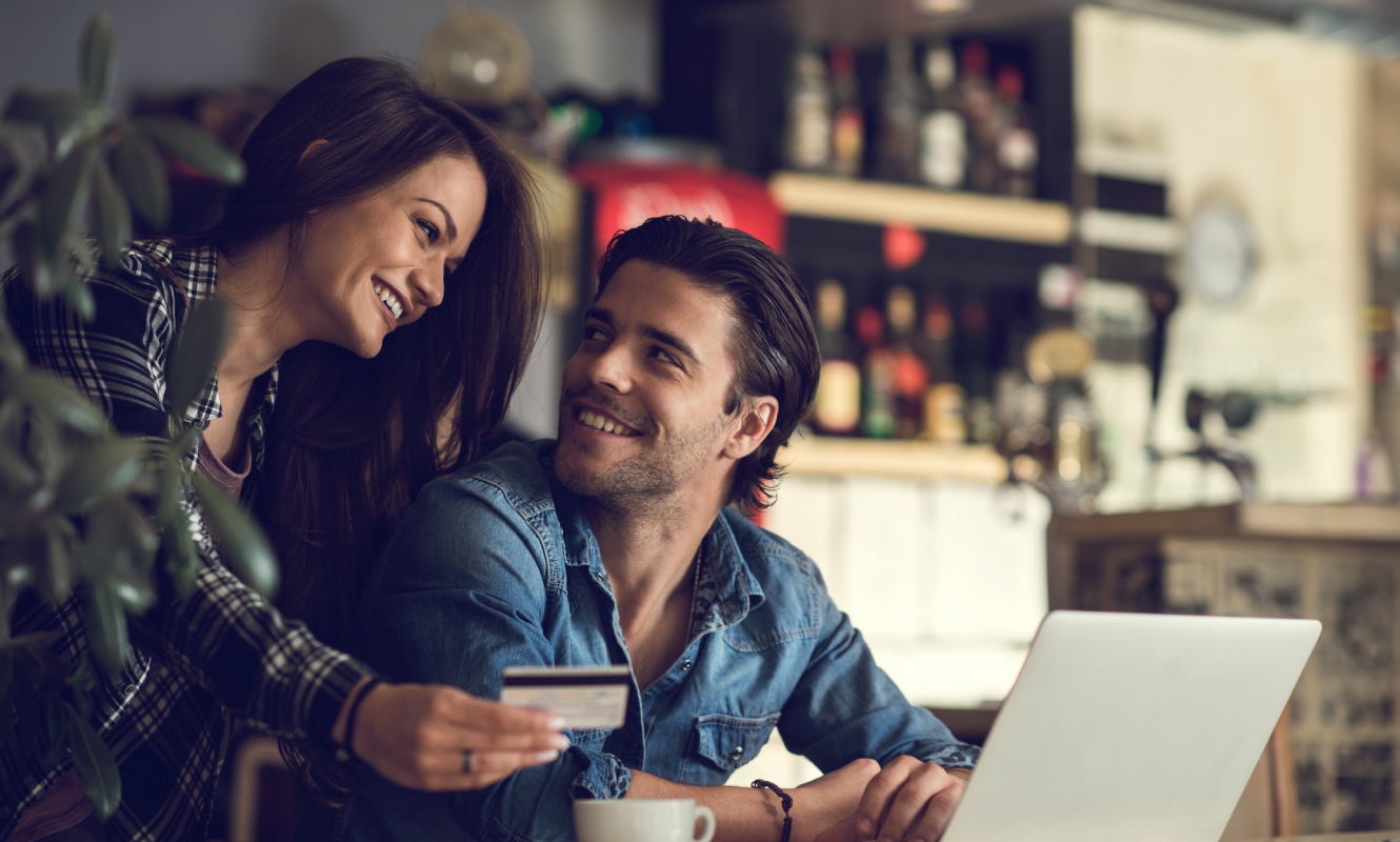 A man and woman in front of a laptop. The woman is holding a credit card. They are both smiling.
