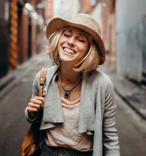 Smiling young woman in a hat standing in a city alley.