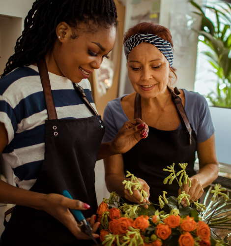 A young woman and an older woman in aprons, they are arranging some flowers.