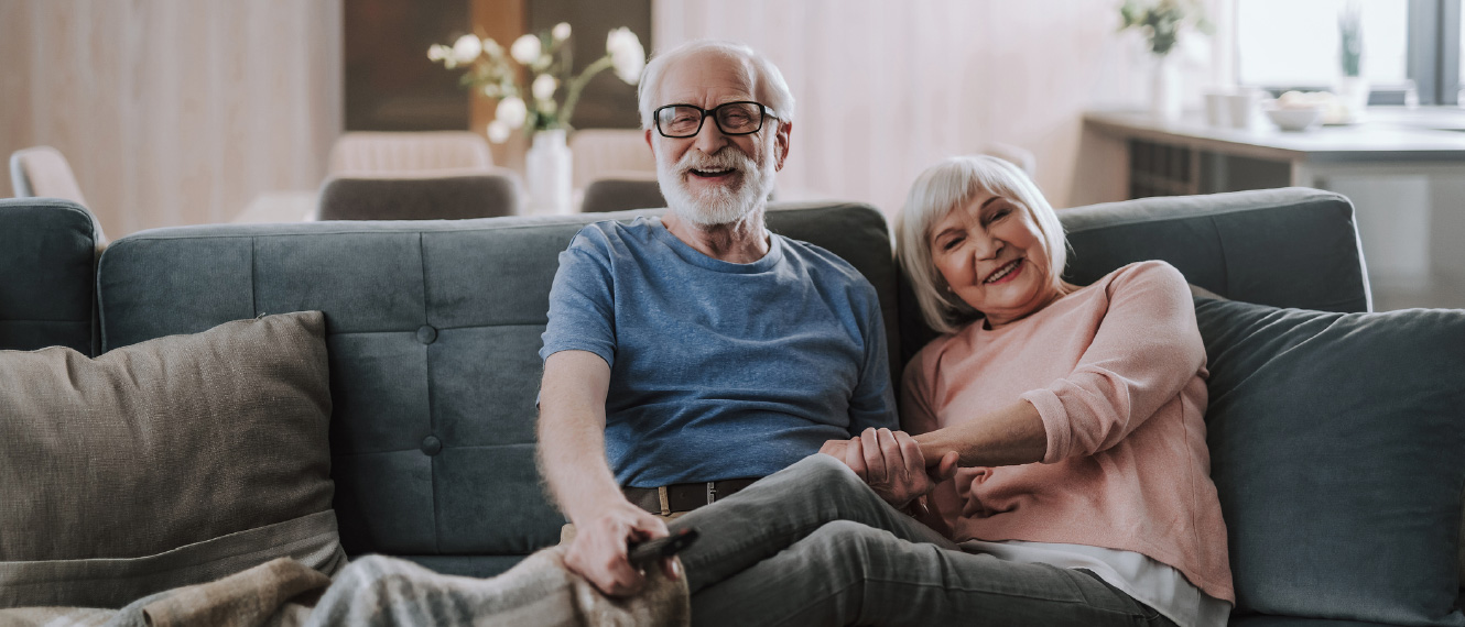 An older couple relaxing on a couch, both are smiling at the camera.
