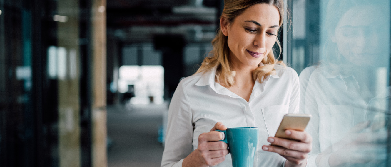 A woman in business attire holding a coffee mug and smartphone.