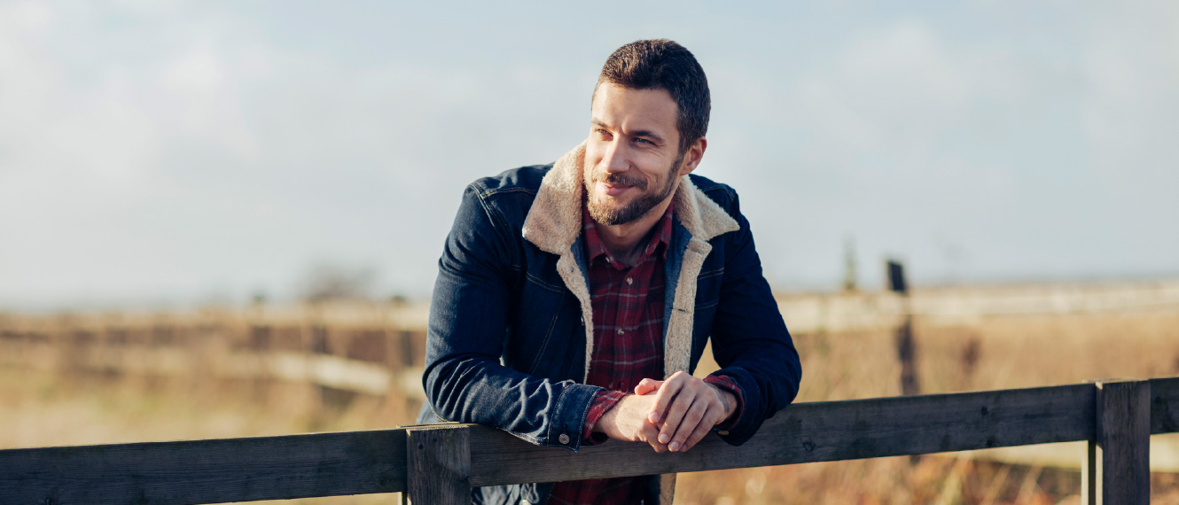 A bearded man in a denim jacket leaning against a wooden fence.