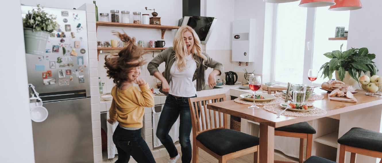A young woman and a teenage girl dancing in a kitchen.